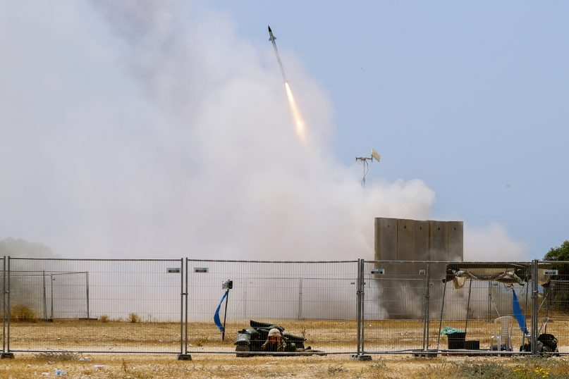 An Israeli soldier takes cover as an Iron Dome air defense system launches to intercept a rocket from the Gaza Strip, in Ashkelon, southern Israel, Tuesday, May 11, 2021. (AP Photo/Ariel Schalit)