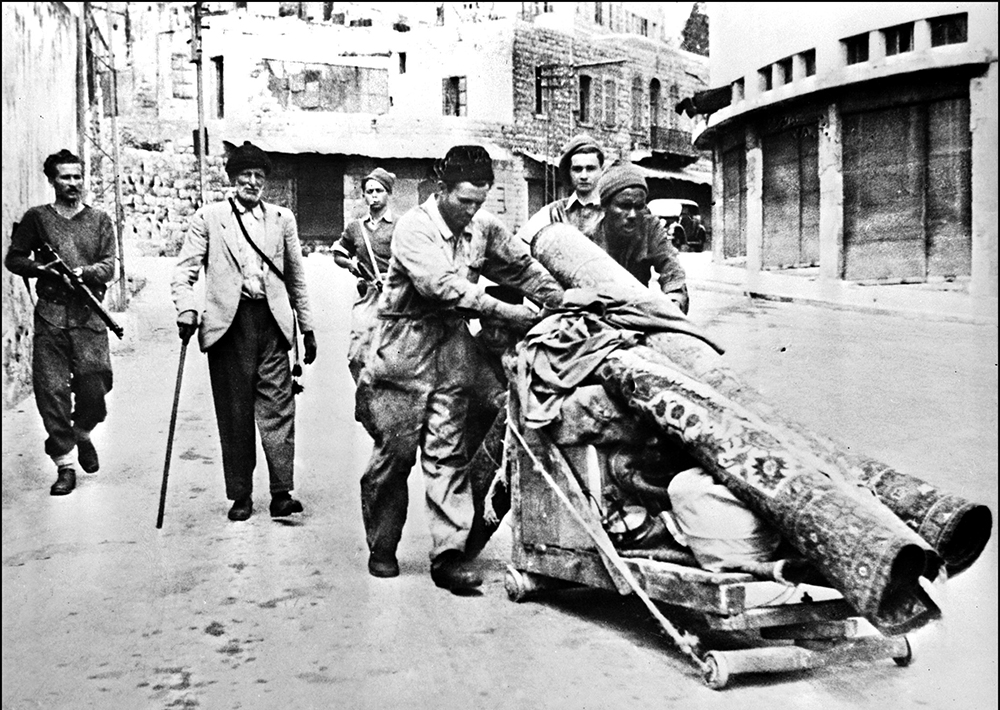 Three members of Haganah, the Jewish Agency self-defence force, escort 12 May 1948 in Haifa three Palestinian Arabs expelled from the city after the Jewish forces took over the harbor 22 April 1948. The 1948-49 first Israeli-Arab War reflected the opposition of the Arab states to the formation of the Jewish state which they considered to be Arab territory. On November 29, 1947, the United Nations' General Assembly voted resolution 181 on the partition of Palestine in two states, one Jewish and one Arab. Jerusalem was to remain under international control. The State of Israel was proclamed on 14 May 1948 by the Jewish National Council and was recognized by the United States and the Soviet Union 15 and 17 May the same year. Arab States of Lebanon, Syria, Jordan, Egypt and Iraq crossed the borders from north, east and south with their regular armies 15 May 1948. Agreements signed in 1949 between Israel and the Arab States ended the 1948 Arab-Israeli War, and established the armistice lines between Israel and the West Bank, also known as the Green Line, until the 1967 Six-Day War. / AFP PHOTO / - (Photo credit should read -/AFP via Getty Images)