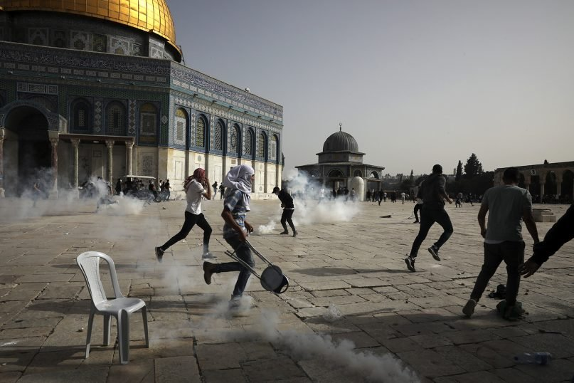 Palestinians run away from tear gas during clashes with Israeli security forces May 10, 2021, at the Al-Aqsa mosque compound in Jerusalem's Old City. (AP Photo/Mahmoud Illean)