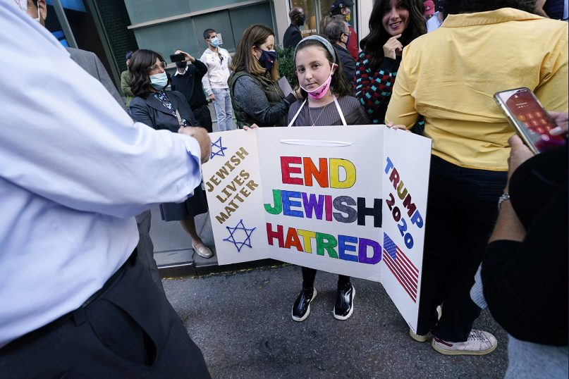 FILE - In this Thursday, Oct. 15, 2020, file photo, a young girl holds a poster she made as she and others joined protesters outside the offices of New York Gov. Andrew Cuomo in New York. Three Rockland County Jewish congregations are suing New York state and Cuomo, saying he engaged in a