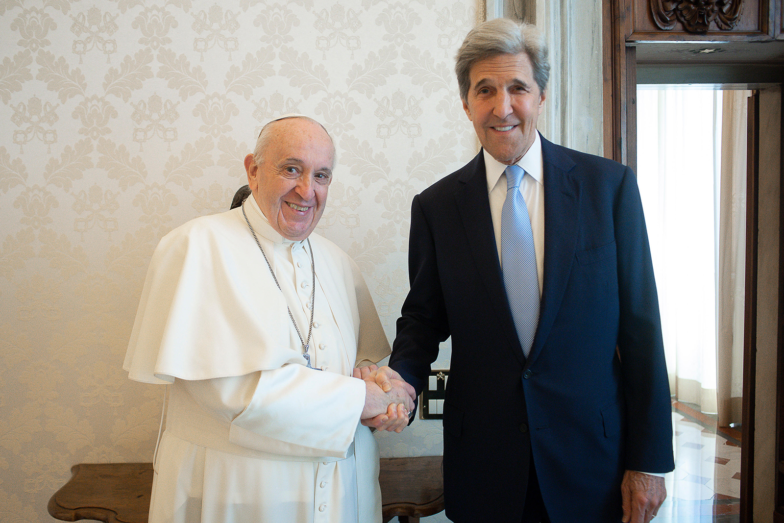 """Pope Francis, left, and John Kerry pose as they meet at the Vatican on May 15, 2021. Kerry, who is President Joe Biden's special envoy on the climate, met privately with the pope Saturday, afterward calling Francis """"a compelling moral authority on the subject of the climate crisis"""" who has been """"ahead of the curve."""" (Photo by Vatican Media)"""