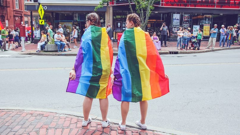 Two females wear rainbow flags during the annual Pride parade in Portland, Maine. Photo by Mercedes Mehling/Unsplash/Creative Commons