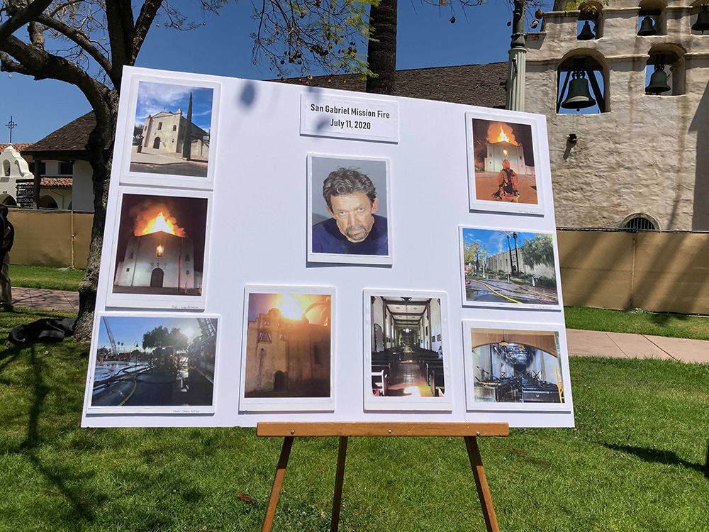 A board displays a mugshot of John David Corey, center, who has been charged in connection with the July 202 fire that destroyed the rooftop of the San Gabriel Mission, officials said during a press conference Tuesday, May 4, 2021, in San Gabriel, California. RNS photo by Alejandra Molina