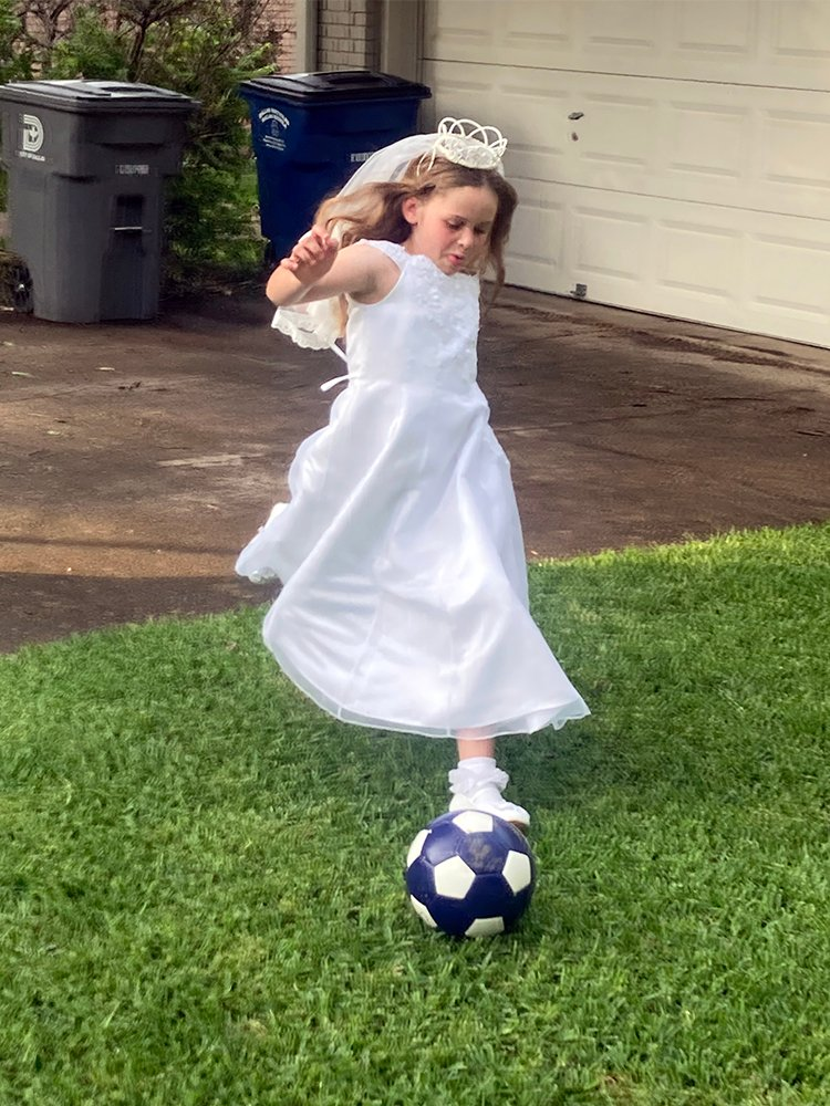 Caroline Perez Hartzel, 8, of Dallas, lets off some pent up energy after her First Holy Communion, Tuesday evening, May 18, 2021. Caroline had just attended Mass for the first time since the pandemic, a special, socially distanced Mass for communicants who studied online all year at St. Thomas Aquinas Catholic Church in East Dallas. Caroline developed a deep love of God in her Family Formation classes, but she also has developed a strong love of soccer that has come roaring back as COVID-19 restrictions end. Photo by Tony Hartzel