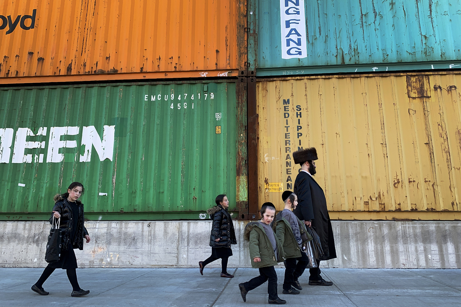 In this Tuesday, March 30, 2021, file photo, members of the Orthodox Jewish community walk past shipping containers in the South Williamsburg neighborhood of Brooklyn, New York. A comprehensive new survey of Jewish Americans finds them increasingly worried about antisemitism and sharply divided about the importance of religious observance in their lives. The wide-ranging survey, released on Tuesday, May 11, 2021, was conducted by the Pew Research Center. (AP Photo/Wong Maye-E)