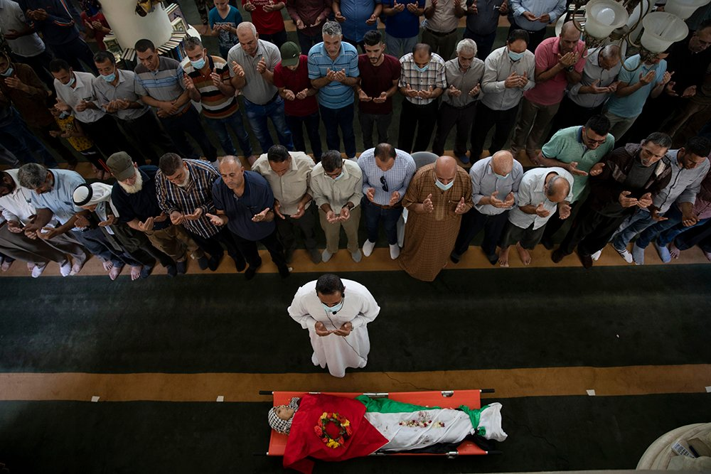 Palestinian mourners pray by the body of Rasheed Abu Arra, who was killed in the clashes with Israeli forces, during his funeral, in the Village of Aqqaba near the West Bank town of Tubas, Wednesday, May 12, 2021. (AP Photo / Majdi Mohammed)