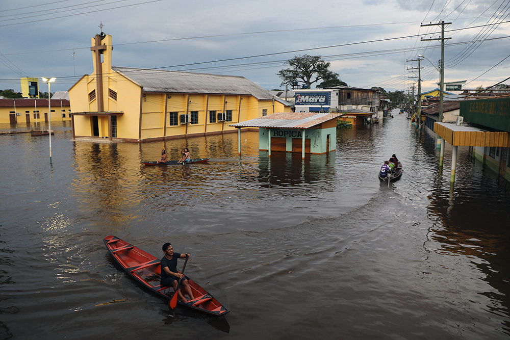Residents paddle through flooded streets past a church in Anama, Amazonas state, Brazil, Thursday, May 13, 2021. (AP Photo/Edmar Barros)