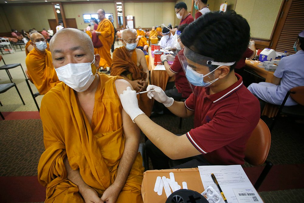 A health worker administers a dose of the Sinovac COVID-19 vaccine to Buddhist monk at Priest Hospital in Bangkok, Thailand, May 18, 2021. Thailand on Friday said it had detected its first locally transmitted cases of the coronavirus variant first found in India, even as it announced the formal rollout of its national vaccination plan from next month. (AP Photo/Anuthep Cheysakron,File)