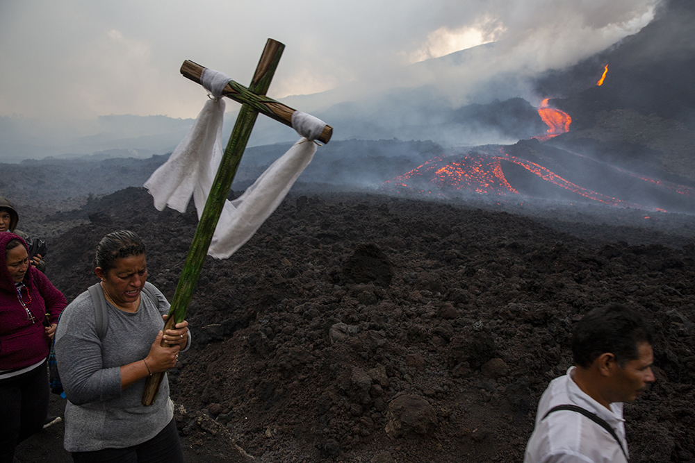 A woman carries a wooden cross during a pilgrimage to pray that the Pacaya volcano decreases its activity, in San Vicente Pacaya, Guatemala, Wednesday, May 5, 2021. The volcano, just 30 miles south of Guatemala's capital, has been active since early February. (AP Photo/Moises Castillo)