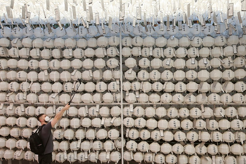 A visitor takes pictures in front of lanterns on the eve of the Buddha's birthday at the Jogye temple in Seoul, South Korea, Tuesday, May 18, 2021. (AP Photo/Ahn Young-joon)
