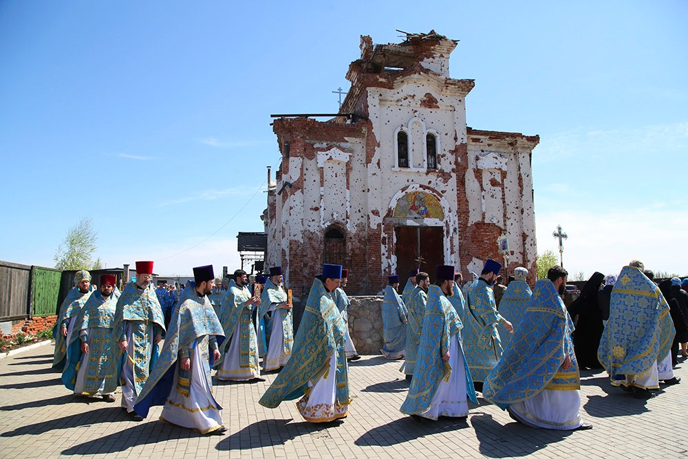 Priests attend a procession celebrating Orthodox Easter at the Iversky Monastery, a monastery of the Ukrainian Orthodox Church (Moscow Patriarchate), damaged by shelling, outside Donetsk, Ukraine, Tuesday, May 4, 2021. (AP Photo/Alexei Alexandrov)