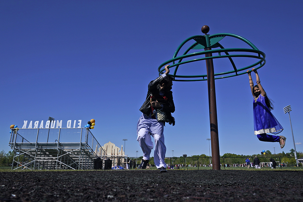 Saif Chaudhry plays with his daughter, Ariana Chaudhry, 8, on a playground near the site of an outdoor celebration of Eid al-Fitr at Overpeck County Park in Ridgefield Park, N.J., Thursday, May 13, 2021. (AP Photo/Seth Wenig)
