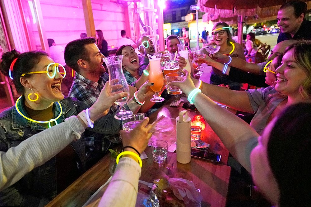 """Emily Baumgartner, left, and Luke Finley, second from left, join friends from their church group in a birthday toast to one of the members during their weekly """"Monday Night Hang"""" gathering at the Tiki Bar on Manhattan's Upper West Side, Monday, May 17, 2021, in New York. """"Most of us live alone and we need community,"""" she said. """"During the pandemic, we started hanging out in the park (Central Park) once a week. Once bars and restaurants reopened, we started coming back to Tiki Bar afterward."""" Under the latest regulations, vaccinated New Yorkers can shed their masks in most situations. Restaurants, shops, gyms and many other businesses can go back to full occupancy if all patrons are inoculated. (AP Photo/Kathy Willens)"""