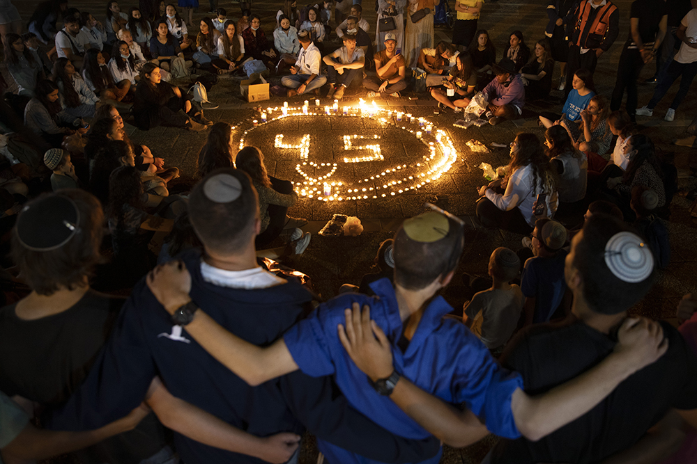 People gather around candles during a vigil in memory of the 45 ultra-Orthodox Jews killed in a stampede at a religious festival in northern Israel on Friday, in Tel Aviv, Israel, Sunday, May 2, 2021. The stampede early Friday cut short the annual festival of Lag b'Omer on Israel's Mount Meron. It was one of the country's deadliest civilian disasters. (AP Photo/Oded Balilty)