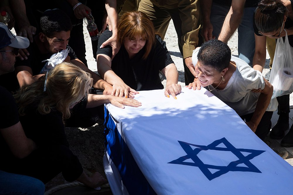 Relatives of Israeli soldier Omer Tabib, 21, mourn during his funeral at a cemetery in the northern Israeli town of Elyakim, Thursday, May 13, 2021. The Israeli army confirmed that Tabib was killed in an anti-tank missile attack near the Gaza Strip, the first Israeli military death in the current fighting between Israelis and Palestinians. (AP Photo/Sebastian Scheiner)