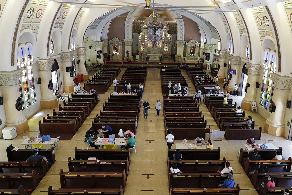 Health workers inoculate residents with the AstraZeneca COVID-19 vaccine inside the Sacred Heart of Jesus Parish church in Quezon City, Philippines, on Monday, May 17, 2021. The church was used to speed up the vaccination process to residents in the area. (AP Photo/Aaron Favila)