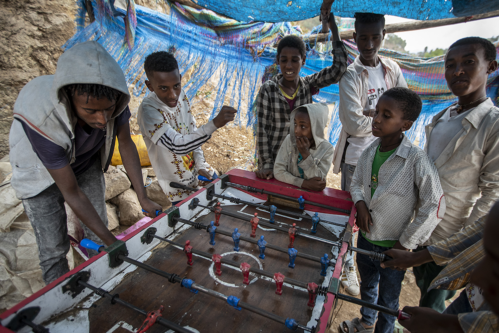 A child punches the air after scoring a goal while playing table football on the street against other children and young men, as Ethiopian Orthodox Christians celebrate Easter Sunday, in Gondar, in the Amhara region of Ethiopia, Sunday, May 2, 2021. (AP Photo/Ben Curtis)