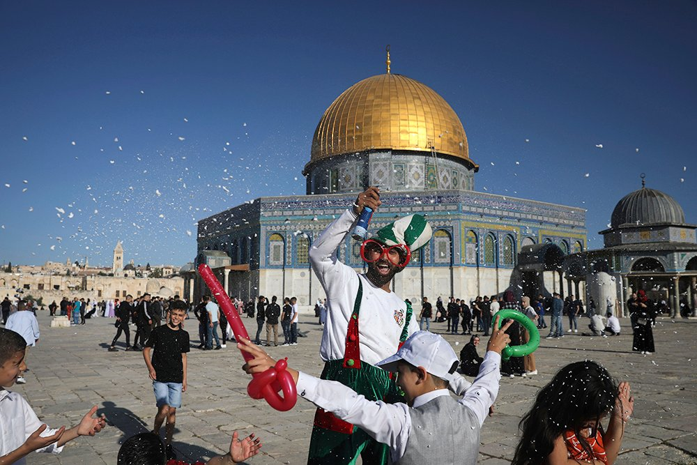A clown sprays children with foam as Muslims gather for Eid al-Fitr prayers at the Dome of the Rock Mosque in the Al-Aqsa Mosque compound in the Old City of Jerusalem, Thursday, May 13, 2021. Eid al-Fitr, festival of breaking of the fast, marks the end of the holy month of Ramadan. (AP Photo/Mahmoud Illean)