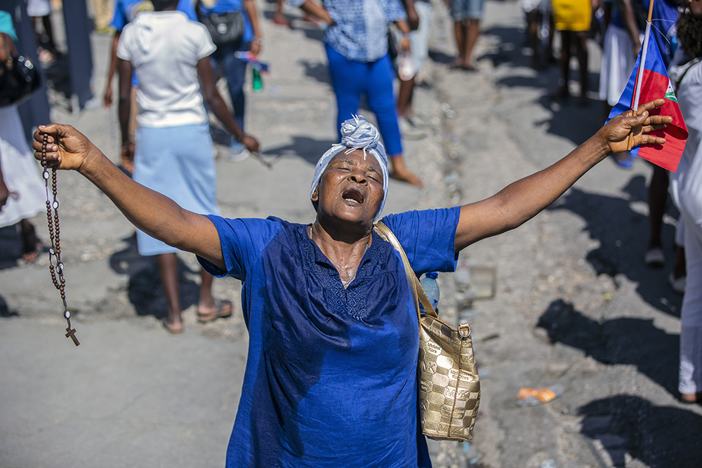 A woman holds out her arms as she prays during a religious march in Port-au-Prince, Haiti, Saturday, May 15, 2021. Hundreds of Haitians marched on the streets of Port-au-Prince after church services on Saturday to collectively pray outdoors for peace and an end to the wave of kidnappings that have victimized the city's residents. (AP Photo/Joseph Odelyn)