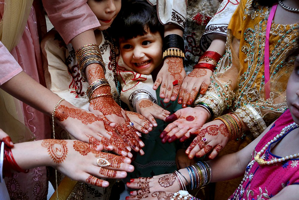 Muslims girls display their hands painted with traditional henna to celebrate Eid al-Fitr holidays, marking on the end of the fasting month of Ramadan, in Peshawar, Pakistan, Thursday, May 13, 2021. (AP Photo/Muhammad Sajjad)