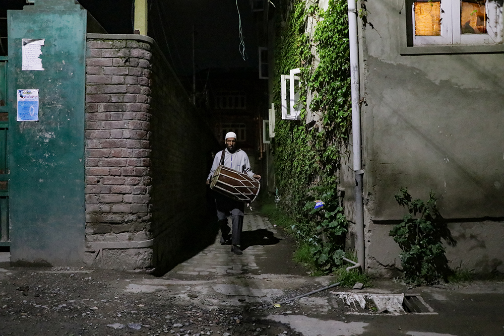 """Mohammad Rafiq Katariya shouts """"Waqt-e-sahar"""" (It's time for Sheri) while beating his drum in a housing lane at Zadibal, a residential area in downtown Srinagar, Kashmir, India, on April 30, 2021, during Ramadan. Photo by Adil Abass"""