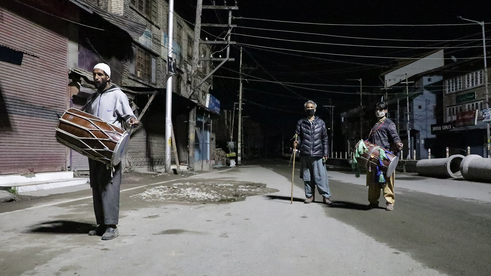 Mohammad Rafiq Katariya, left, and his colleagues beat their drums to wake Muslims at Sehri time in Alamgari Bazar Chowk, an old residential area in Srinagar, Kashmir, India, on April 30, 2021. Photo by Adil Abass