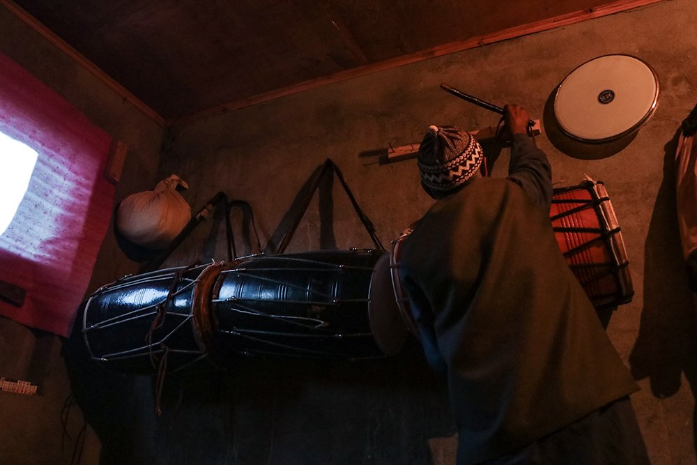 Manzoor Ahmed Lassi hangs up his drum in Srinagar, Kashmir, India, after returning from midnight drumming to have his own pre-dawn meal to observe fast. Photo by Adil Abass