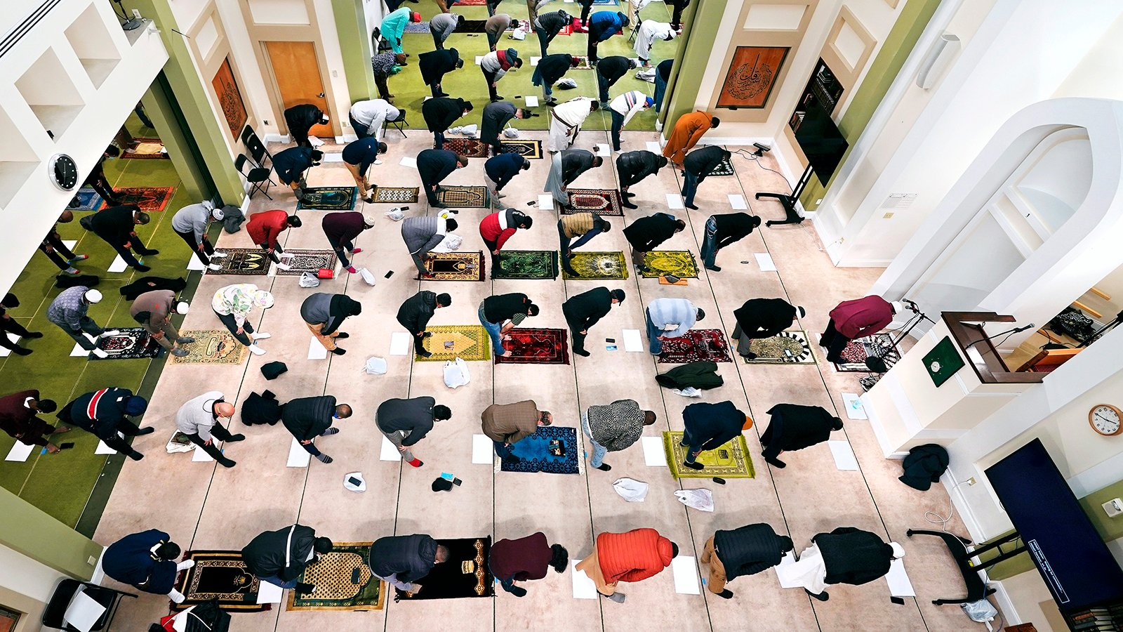 Worshippers, socially distanced due to COVID-19 concerns, bow in prayer at the Islamic Society of Boston during the first Friday of the holy month of Ramadan, April 16, 2021, in Boston. (AP Photo/Charles Krupa)