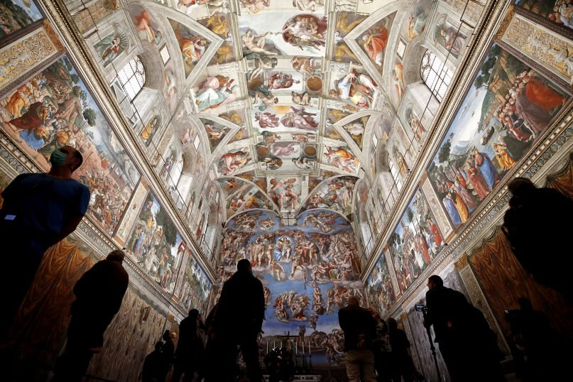 Visitors admire the Sistine Chapel inside the Vatican Museums on the occasion of the museum's reopening, in Rome, May 3, 2021. The Vatican Museums reopened to visitors after a shutdown for COVID-19 containment measures. (AP Photo/Alessandra Tarantino)