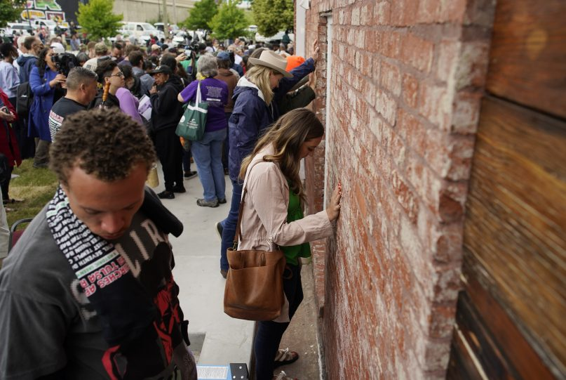 People hold their hands on a prayer wall outside of the historic Vernon African Methodist Episcopal Church in the Greenwood neighborhood during the centennial of the Tulsa Race Massacre, Monday, May 31, 2021, in Tulsa, Okla. The church was largely destroyed when a white mob descended on the prosperous Black neighborhood in 1921, burning, killing, looting and leveling a 35-square-block area. (AP Photo/John Locher)