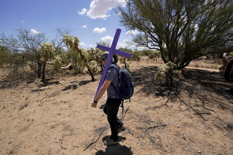 Alyssa Quintanilla, part of the Tucson Samaritans volunteer group, carries a cross May 18, 2021, to be installed at the site where a migrant died in the desert some time ago,  near Three Points, Arizona. Protecting migrants and honoring the humanity of those who died on the perilous trail is a kind of religion in southern Arizona, where spiritual leaders four decades ago founded the Sanctuary Movement, a campaign to shelter Central Americans fleeing civil war, and scores of volunteers carry on their legacy today. (AP Photo/Ross D. Franklin)