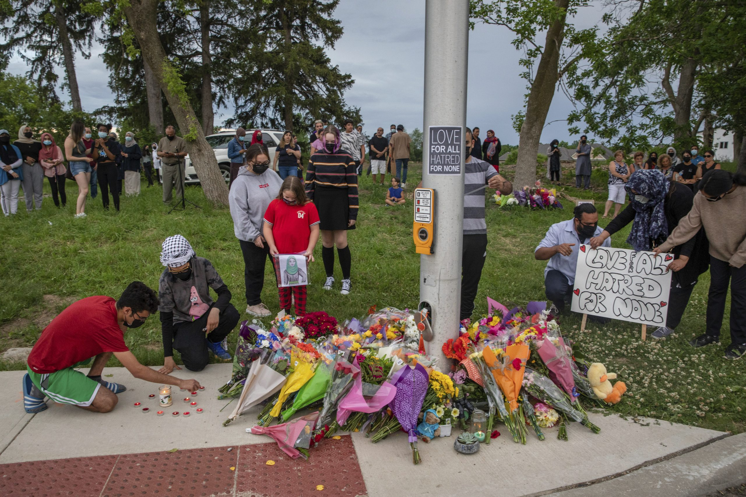 People attend a memorial at the location where a family of five was hit by a driver in London, Ontario, on June 7, 2021. Four members of the family died and one is in critical condition. A 20-year-old man has been charged with four counts of first-degree murder and a count of attempted murder in connection with the crime. (Brett Gundlock/The Canadian Press via AP)