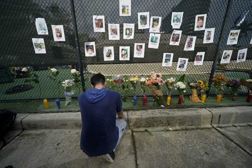 Leo Soto, who created this memorial with grocery stores donating flowers and candles, pauses in front of photos of some of the missing people that he put on a fence, near the site of an oceanfront condo building that partially collapsed in Surfside, Florida, June 25, 2021. (AP Photo/Gerald Herbert)
