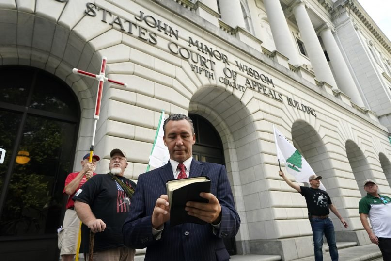 Tony Spell, pastor of the Life Tabernacle Church of Central City, Louisiana, waits outside the 5th Circuit Court of Appeals in New Orleans on June 7, 2021. Spell, who flouted coronavirus restrictions last year, prepared Monday to ask the court to revive his lawsuit challenging the restrictions. (AP Photo/Gerald Herbert)