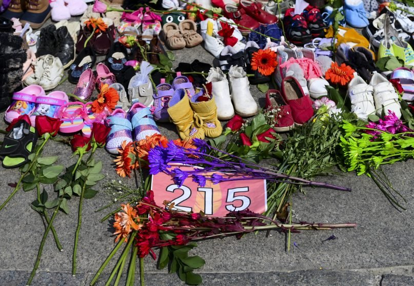 Flowers, children's shoes and other items rest at a memorial at the Eternal flame on Parliament Hill in Ottawa on Tuesday, June 1, 2021, in recognition of the discovery of children's remains at the site of a former residential school in Kamloops, British Columbia. (Sean Kilpatrick/The Canadian Press via AP)