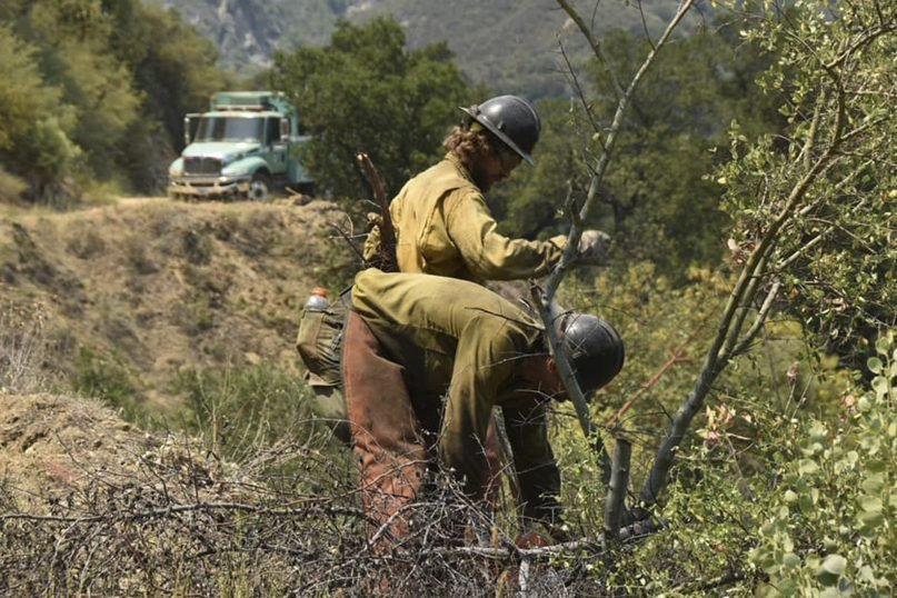 In this photo provided by the California Interagency Willow Fire Incident, firefighters work in steep terrain at the Willow Fire near Big Sur, Calif., on Sunday, June 20, 2021. Dozens of wildfires were burning in hot, dry conditions across the U.S. West. In California, firefighters still faced the difficult task of trying to contain a large forest fire in rugged coastal mountains south of Big Sur that forced the evacuation of a Buddhist monastery and nearby campground. (California Interagency Willow Fire Incident via AP)