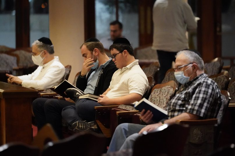 Jewish faithful pray at the Shul of Bal Harbour after members of the community were reported missing in the partial collapse of a 12-story beachfront condo, Thursday, June 24, 2021, in the Surfside area of Miami.(AP Photo/Gerald Herbert)