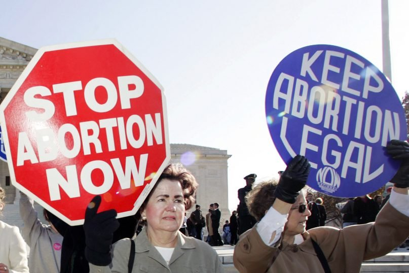 In this Nov. 30, 2005, file photo, an anti-abortion demonstrator stands next to an abortion-rights supporter outside the U.S. Supreme Court in Washington. (AP Photo/Manuel Balce Ceneta)