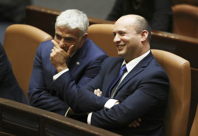 Israel's new prime minister, Naftali Bennett, sits with Yair Lapid, left, during a Knesset session in Jerusalem on June 13, 2021. Israel's parliament has voted in favor of a new coalition government, formally ending Prime Minister Benjamin Netanyahu's historic 12-year rule. Bennett, a former ally of Netanyahu, became the new prime minister. (AP Photo/Ariel Schalit)