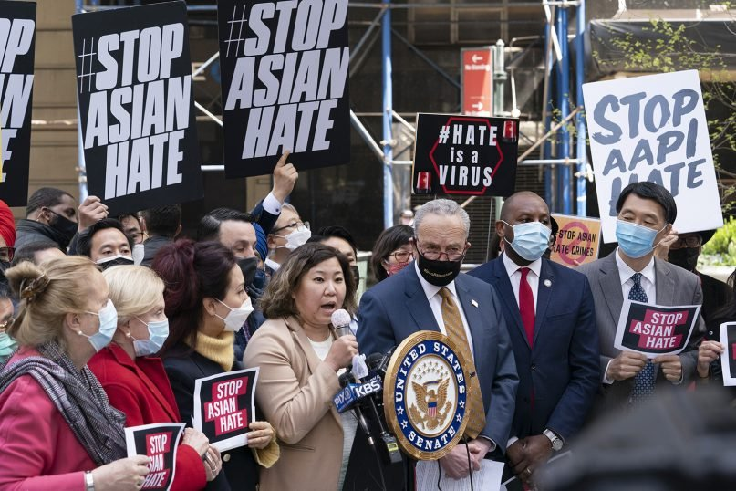 """U.S. Rep.GraceMeng, D-N.Y., center, is joined by Senate Majority Leader Chuck Schumer, D-N.Y., at a news conference to discuss an Asian American hate crime bill, April 19, 2021, in New York. """"For more than a year, the Asian American community has been fighting two crises — the COVID-19 pandemic and the anti-Asian hate,"""" said Meng. (AP Photo/Mark Lennihan)"""