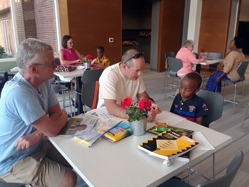 Tom Griggs, left, and Joe Meadows use their skills to help refugee child Kevin, right, learn English at Fifth Reformed Church in Grand Rapids, Michigan. Photo courtesy of David Lubbers