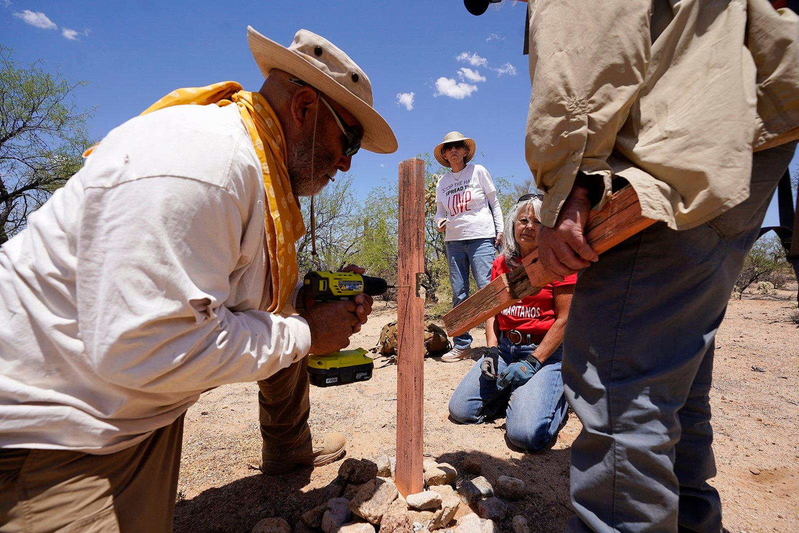 From left, Peter Lucero, Eileen O'Farrell Smith, Terry Stanford and Alvaro Enciso, all volunteers for the Tucson Samaritans, try to repair a damaged cross marking the site of a deceased migrant in the desert near Three Points, Ariz., on Tuesday, May 18, 2021. (AP Photo/Ross D. Franklin)