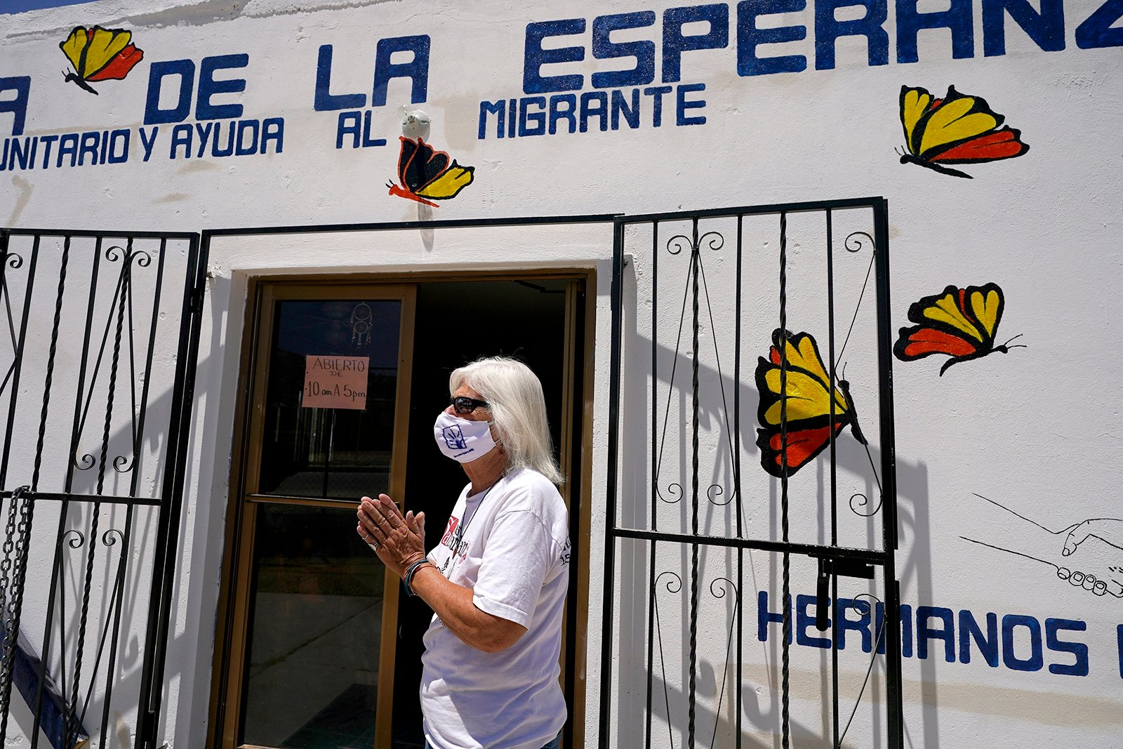 """Gail Kocourek, of the Tucson Samaritans volunteer group, pauses as she speaks with migrants in front of Casa de la Esperanza, a new migrant help center just south of the border in the Mexican town of Sasabe on Wednesday, May 19, 2021. """"I don't think anyone deserves to die for trying to make a better life for their family,"""" Kocourek says. (AP Photo/Ross D. Franklin)"""