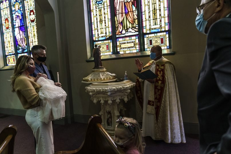 Natalia, left, and Chris Dobosz stand with their 4-month-old daughter, Olivia; 3-year-old daughter, Sophia, bottom; and Chris' father, Marion Dobosz, right, at Olivia's baptism during a service in Polish by the Rev. Dariusz Jonczyk at St. Joseph's Church in Central Falls, Rhode Island, on April 4, 2021. The couple lost their uncle and his wife within a week of each other to COVID-19. They had put off the baptism until more of the family could get vaccinated and it felt safer to gather. Jonczyk says he lost 22 members of his congregation to the virus. (AP Photo/David Goldman)