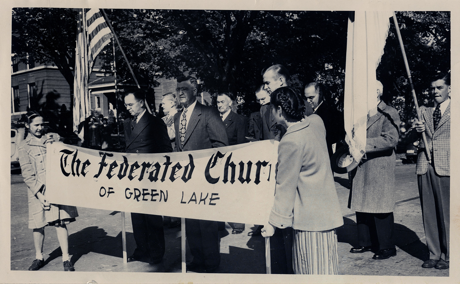 The new replaces the old as these two girls unfurl a scroll, covering the names of the three former separate churches in 1948 in Green Lake, Wisconsin. The unrolling of the Federated Church scroll signaled the three congregations, Congregational, Baptist and Methodist, to move forward to unite. The scroll bearers are Marion Palmer, left, and Roxanna Thrall. RNS archive photo by A.W. Grube. Photo courtesy of the Presbyterian Historical Society