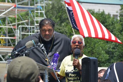 Pam Garrison, co-chair of the West Virginia Poor People's Campaign, speaks during beside Rev. William Barber II during the protest on Wednesday, June 23, 2021. RNS photo by Jack Jenkins