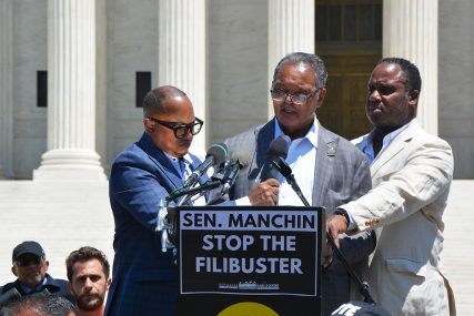Rev. Jesse Jackson, center, speaks from the podium in a push for the passing of new voting rights legislation on Wednesday, June 23, 2021 outside the Supreme Court. RNS photo by Jack Jenkins