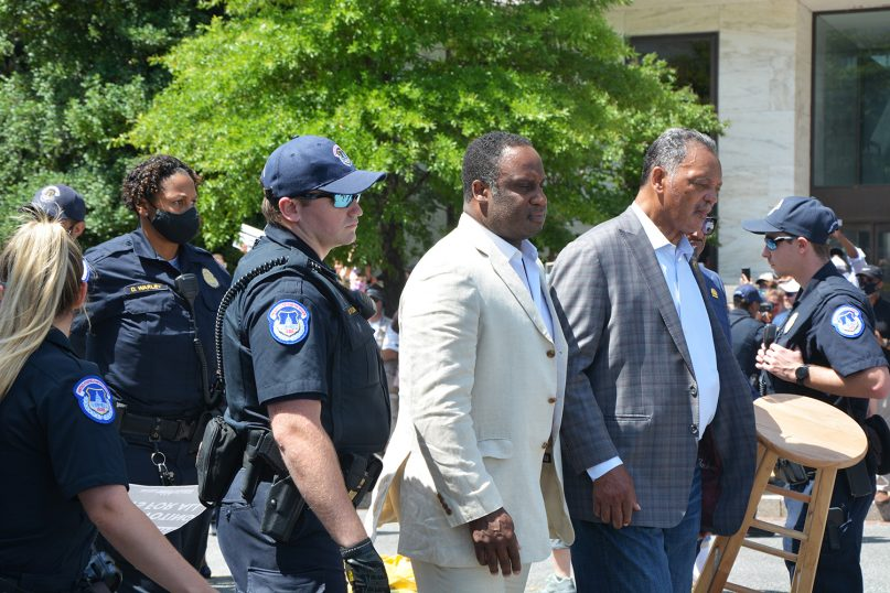 The Rev. Jesse Jackson, right, is arrested during a protest on June 23, 2021, outside the Hart Senate Building. The Rev. William Barber II was also arrested. RNS photo by Jack Jenkins
