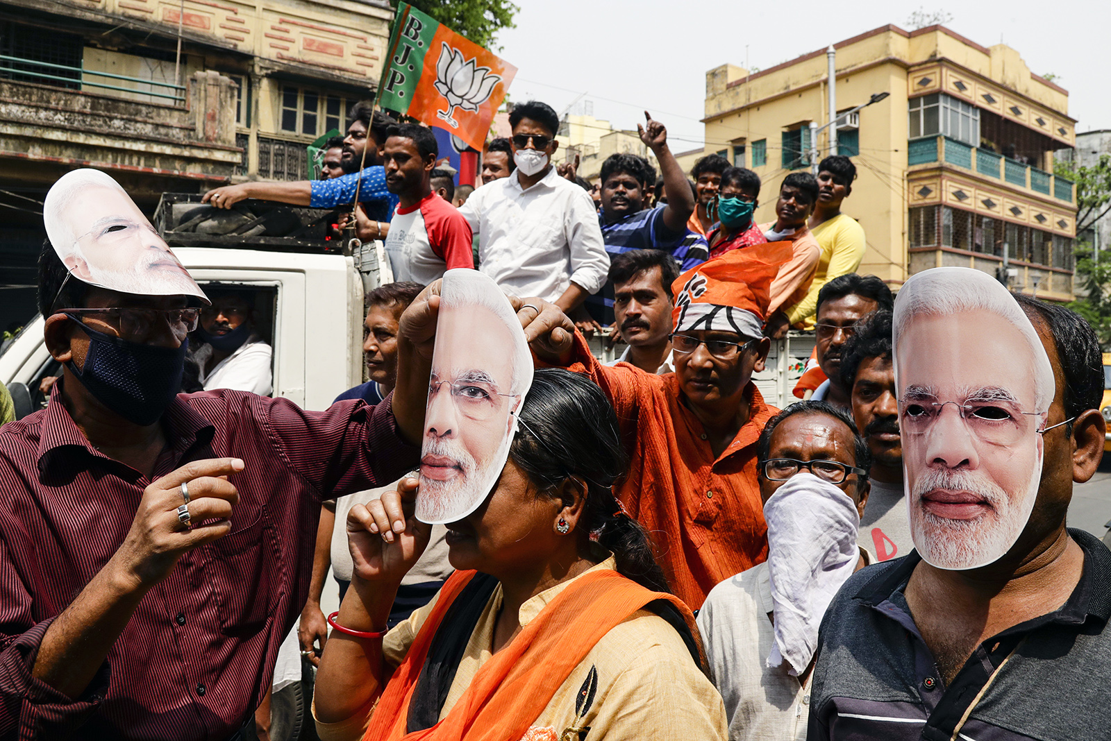In this March 20, 2021, file photo, supporters of Bharatiya Janata Party wear masks bearing the likeness of Prime Minister Narendra Modi during a campaign rally ahead of elections in West Bengal state in Kolkata, India. Despite clear signs that India was being swamped by another surge of coronavirus infections, Modi refused to cancel the rallies, a major Hindu festival and cricket matches with spectators. The burgeoning crisis has badly dented Modi's carefully cultivated image as an able technocrat. (AP Photo/Bikas Das, File)