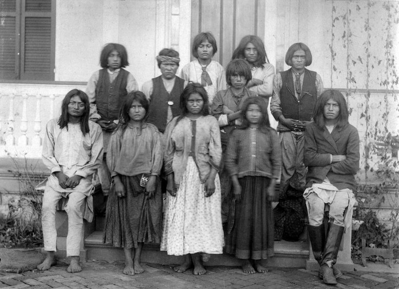 Native American (Chiricahua Apache) boys and girls pose outdoors at the Carlisle Indian Industrial School in Carlisle, Pennsylvania, after their arrival from Fort Marion, Florida, in November 1886. Photo by J. N. Choate/Creative Commons